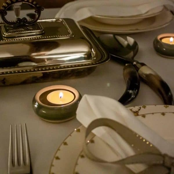 Lit tealights inside tealight holders on a dinner table setting.