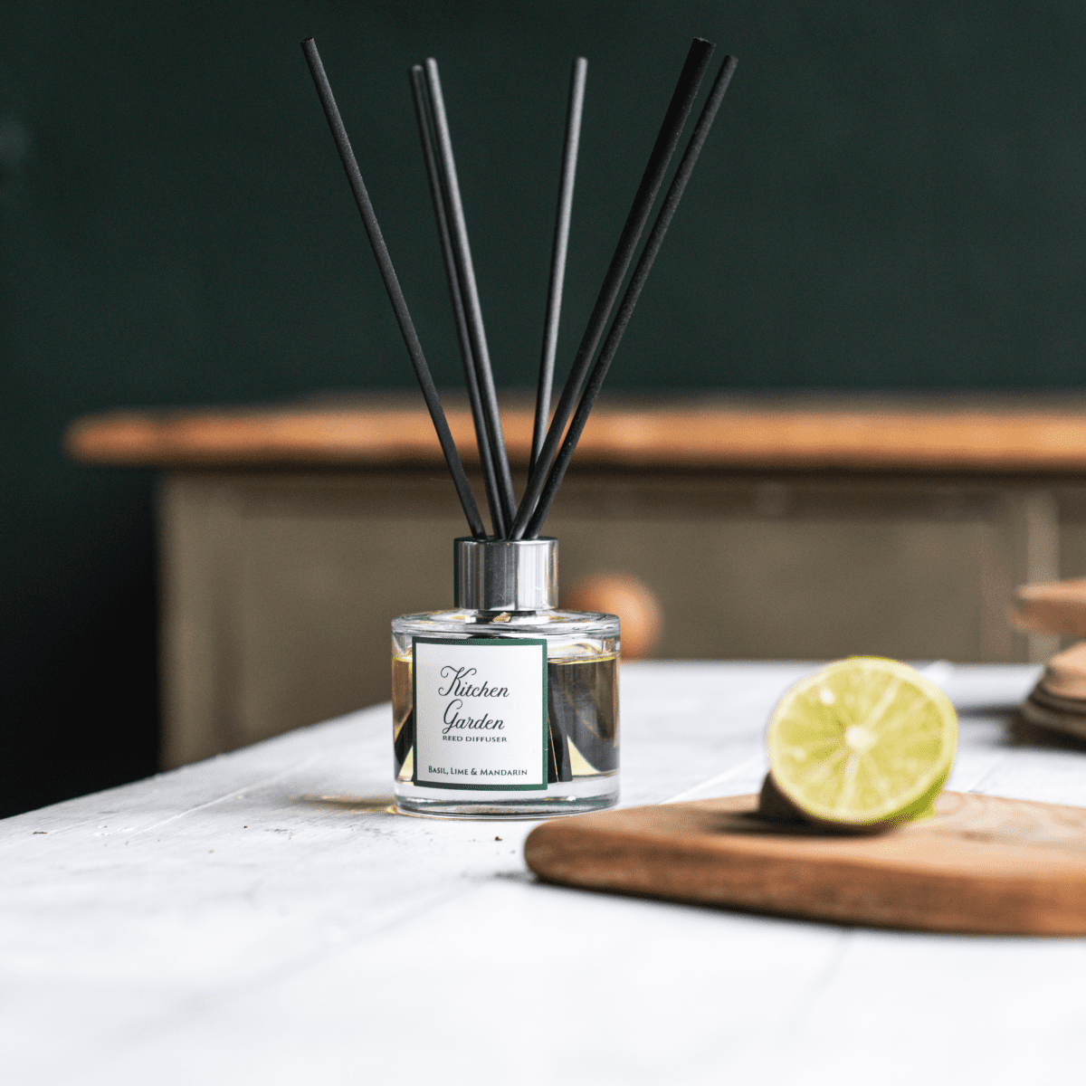 Kitchen Garden diffuser bottle containing black fibre reeds on a kitchen worktop. Wooden chopping board on the right hand side with half a lime.