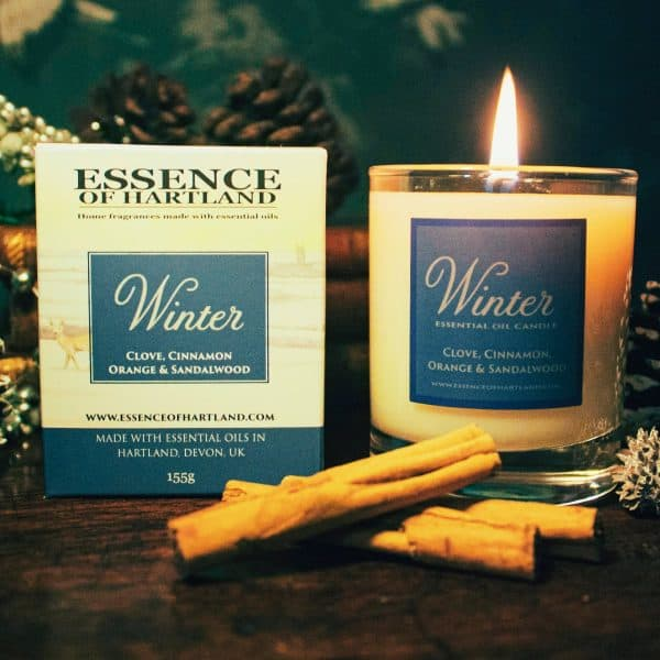 Lit Winter candle next packaging and cinnamon sticks in front.