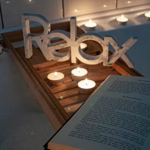 winter tealights next to a relax sign over a bath