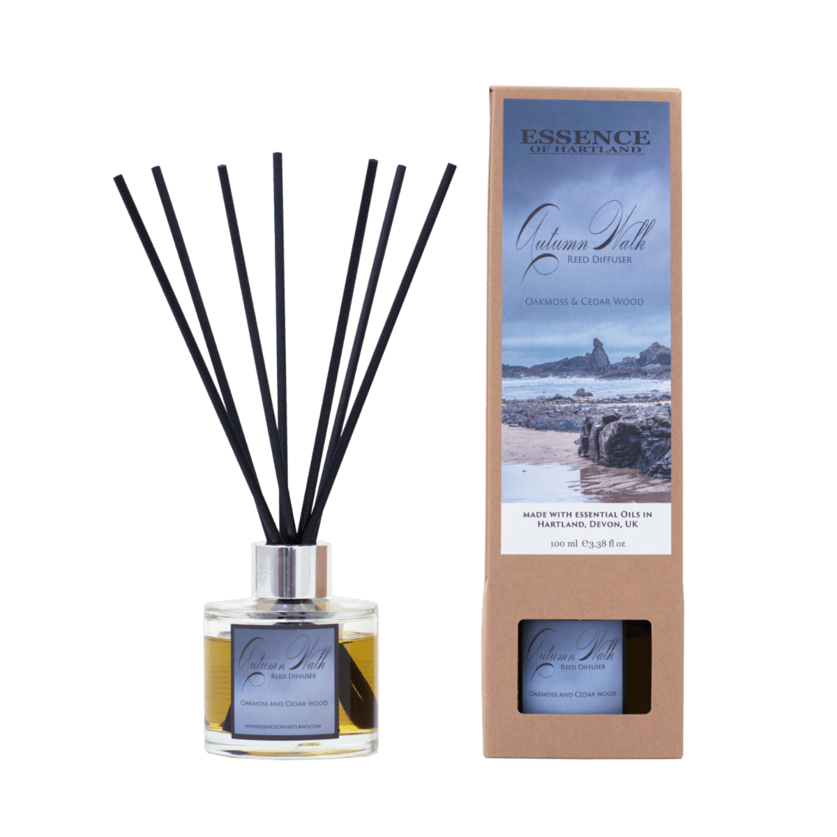 A glass diffuser bottle of Autumn Walk with black fibre reeds, in the middle the diffuser box packaging detailing the name of the product and image of Bear Rock and moody Hartland Quay beach scene.