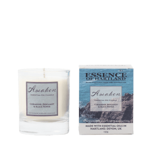 Glass votive candle labelled Awaken next to packaging featuring rocks off Hartland Quay on a sunny day.