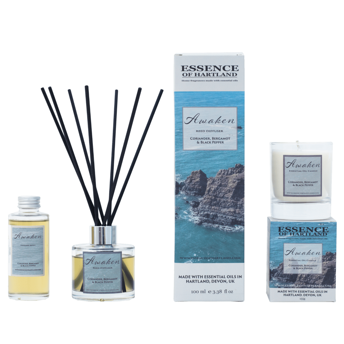A group of Awaken products. A glass bottle of Awaken refills on the right, then a glass diffuser bottle of Awaken with black fibre reeds, in the middle the diffuser box packaging detailing the name of the product and an image of some rocks surrounded by the sea, a similar image is on the box packaging for the candle on the right hand side with the candle sat on top.