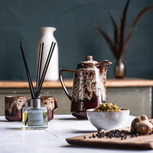 Table setting with a chopping board in the foreground on the right hand side with some black peppercorns, ginger and a ceramic bowl of coriander. On the left hand side a glass diffuser bottle of Awaken with black fibre reeds. Behind the diffuser are two brown 70's style cups and a coffee pot.
