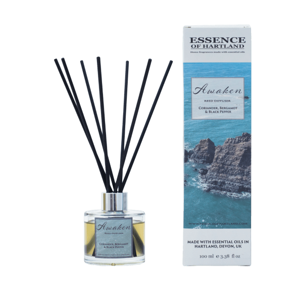 A glass diffuser bottle of Awaken with black fibre reeds, in the middle the diffuser box packaging detailing the name of the product and an image of some rocks surrounded by the sea.