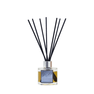 Glass diffuser bottle labelled Autumn Walk with black fibre reeds.