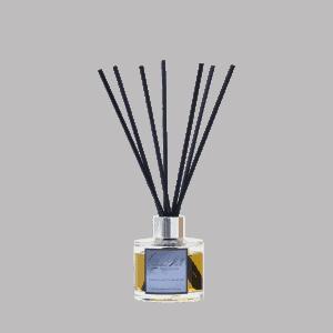 Glass diffuser bottle labelled Autumn Walk with black fibre reeds.