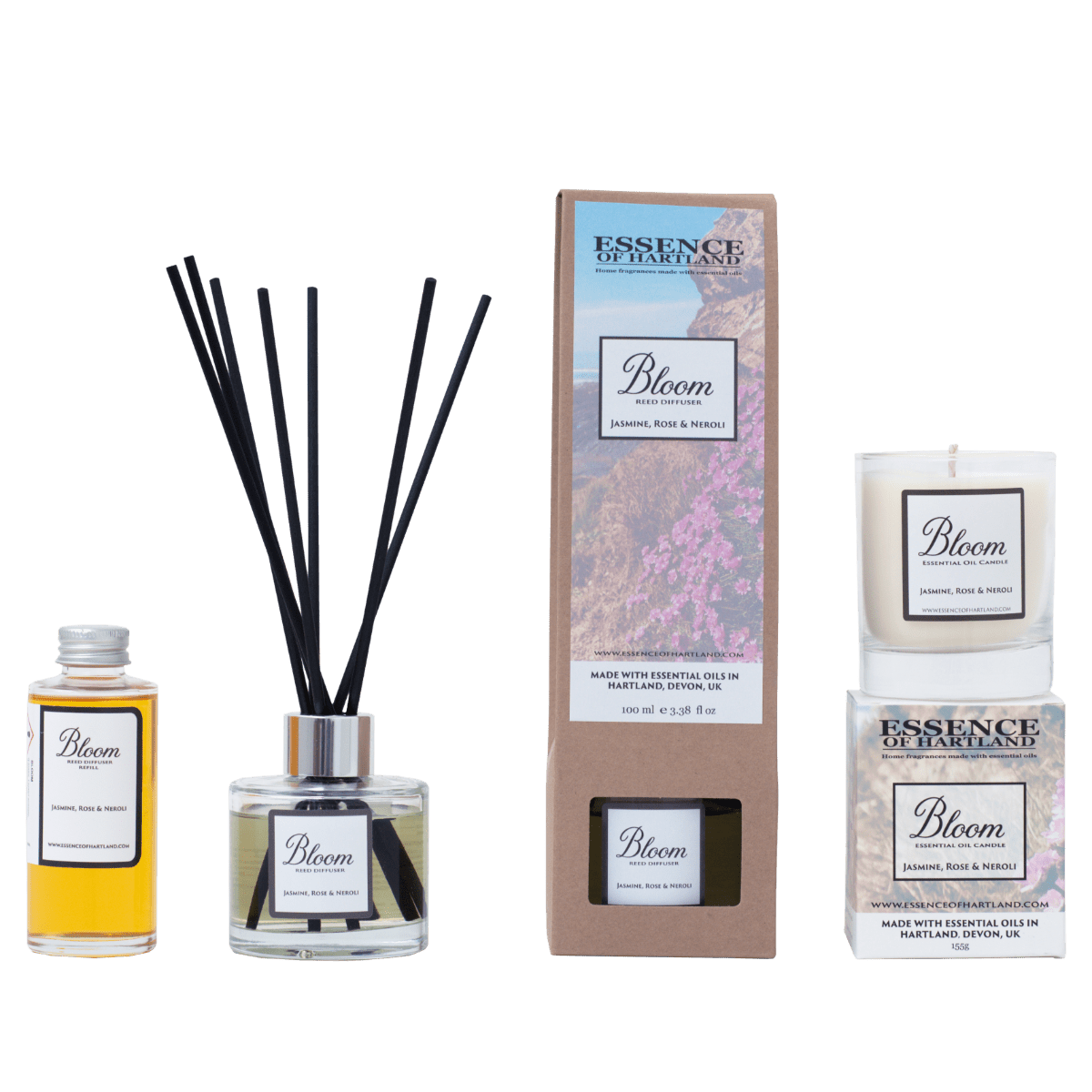 A group of Bloom products. A glass bottle of Bloom refill on the right, then a glass diffuser bottle of Bloom with black fibre reeds, in the middle the diffuser box packaging detailing the name of the product and image of flowers on cliffs looking down to Welcombe Beach, a similar image is on the box packaging for the candle on the right hand side with the candle sat on top.
