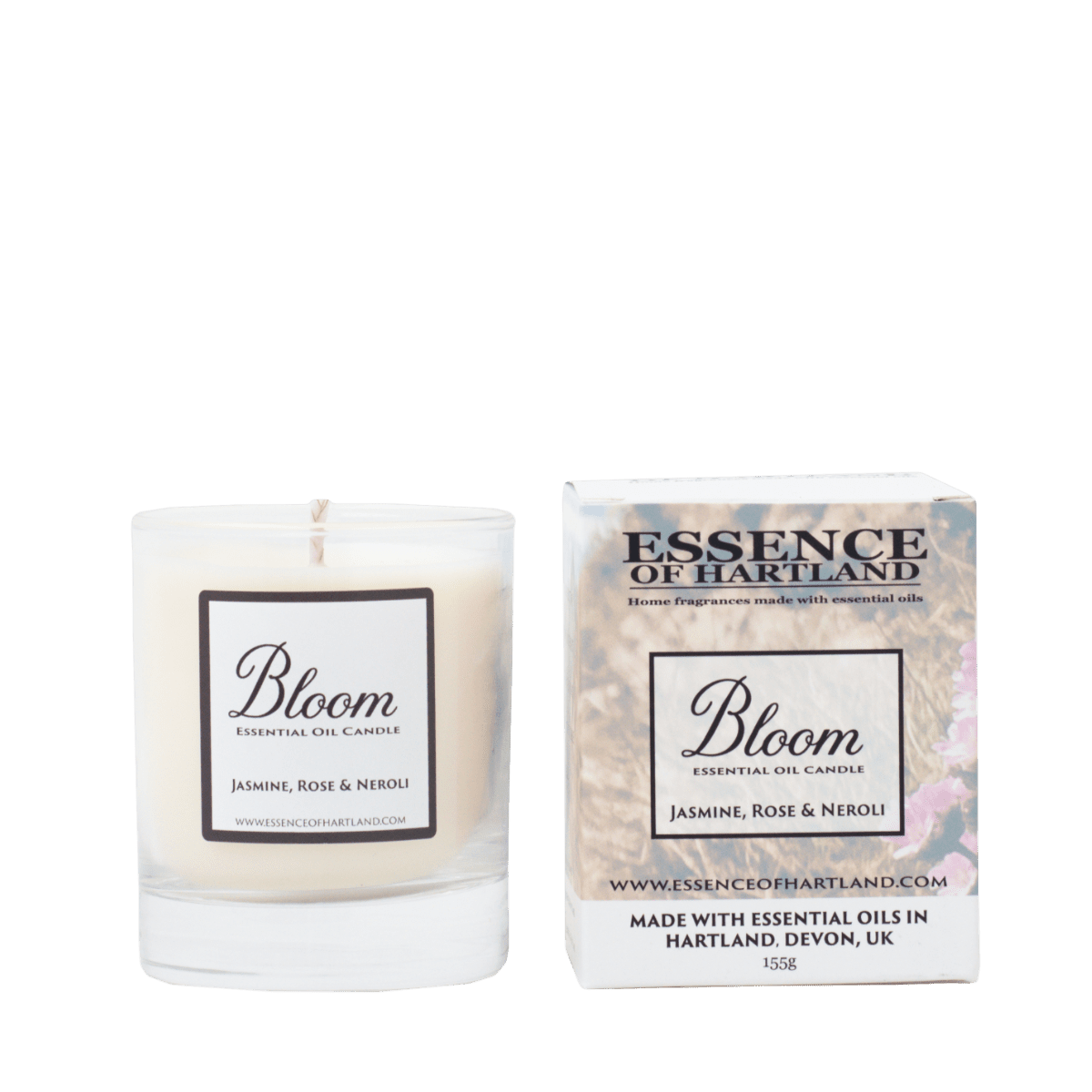 Glass votive candle labelled Bloom, next to packaging featuring a floral hillside looking down to Welcombe beach.
