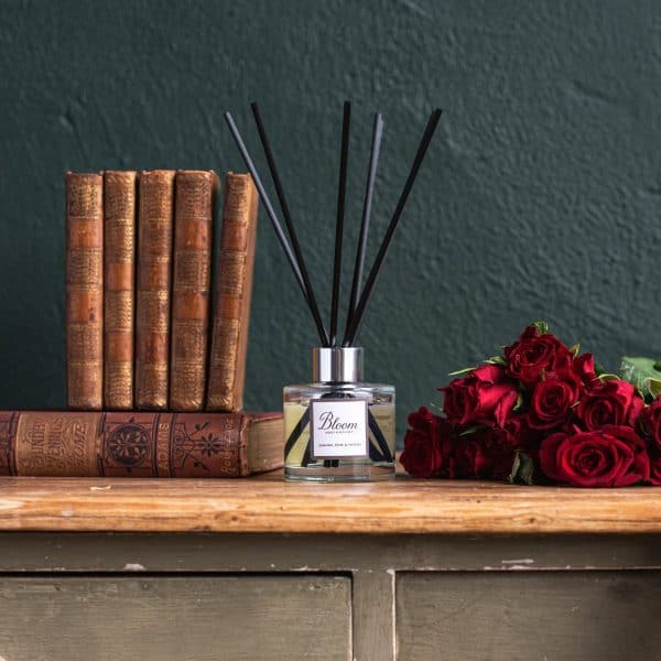 Bloom diffuser bottle with black fibre reeds next to some red roses and antique books. On the right hand side of the bottle are red roses.