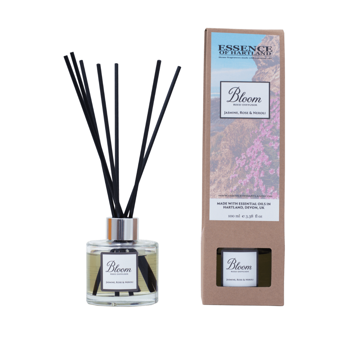 Glass diffuser bottle of Bloom with black fibre reeds, in the middle the diffuser box packaging detailing the name of the product and image of flowers on cliffs looking down to Welcombe Beach.