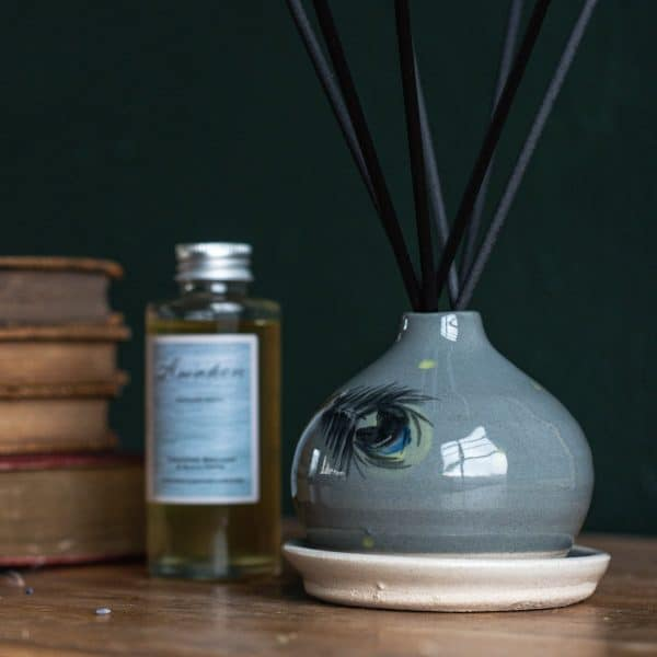 Ceramic diffuser vase with peacock feather design containing black fibre reeds and sat on a ceramic dish. A glass bottle of Awaken diffuser refill on the left hand side just next to some antique books