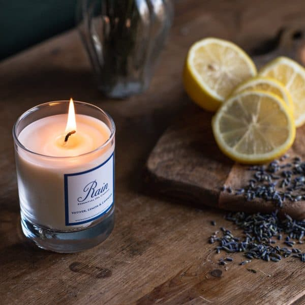 Lit Rain candle from above with sliced lemons on a wooden chopping board and dried lavender.