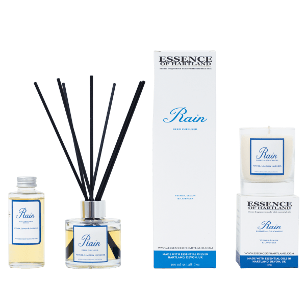 A group of Rain products. A glass bottle of Rain refill on the right, then a glass diffuser bottle of Rain with black fibre reeds, in the middle the diffuser box packaging detailing the name of the product. The candle packaging on the right hand side with the candle sat on top.