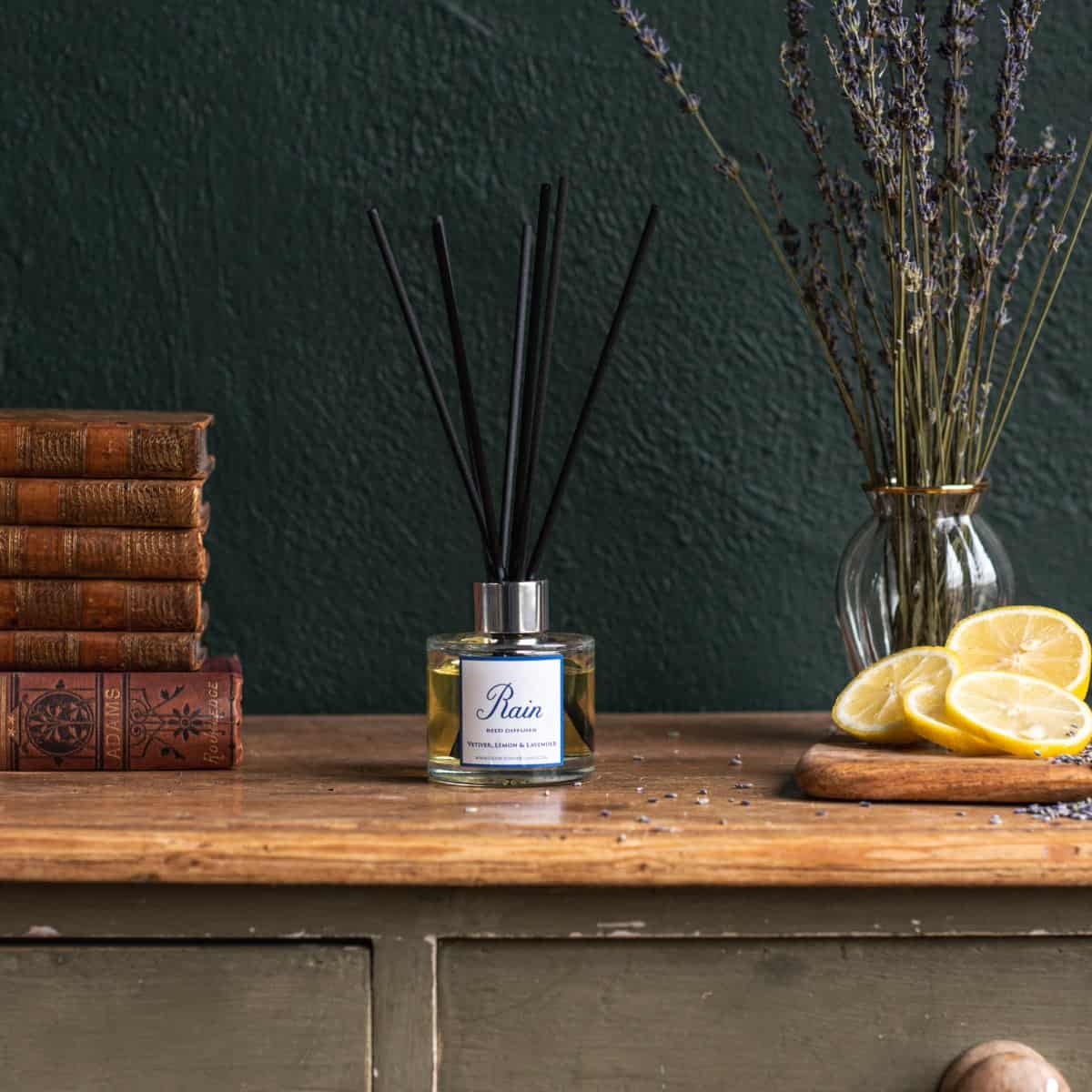 Rain diffuser bottle with black fibre reeds sat on top of a wooden rustic chest with antique books on the left hand side and glass vase of lavender on the right hand side. Sliced lemons in front of the vase.