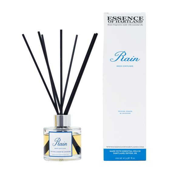 A glass bottle of Rain refill on the right, then a glass diffuser bottle of Rain with black fibre reeds, in the middle the diffuser box packaging detailing the name of the product.