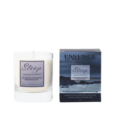 Glass votive candle with Sleep written on the label, next to the packaging featuring a moody image of Hartland Quay.