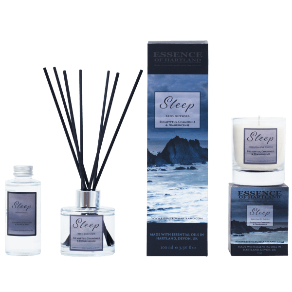 A group of Sleep products. A glass bottle of Sleep refill on the right, then a glass diffuser bottle of Sleep with black fibre reeds, in the middle the diffuser box packaging detailing the name of the product and moody image of Hartland Quay, a similar image is on the box packaging for the candle on the right hand side with the candle sat on top.