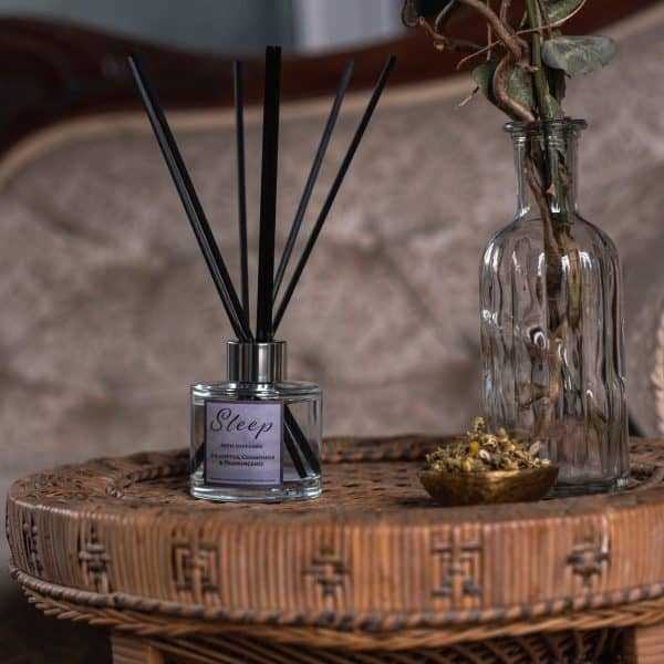 Rattan round table with a glass diffuser bottle containing black fibre reeds and label with Sleep written on it. On the right hand side a small bowl of camomile flowers and tall glass bottle with eucalyptus flowers.