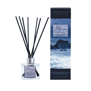 Glass diffuser bottle of Sleep with black fibre reeds, in the middle the diffuser box packaging detailing the name of the product and moody image of Hartland Quay.
