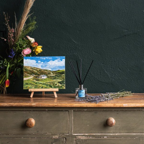 Rustic wooden chest of drawers with oil painting of Blackpool Mill Cottage in Hartland on a small wooden easel on top with dried flowers behind. In the middle a lit candle labelled Spring and some dried lavender laid out on the right hand side.