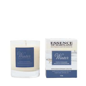 Glass votive candle with label Winter Essential Oil Candle, next to packaging detailing the name of the product and an image of two stags in the snow.