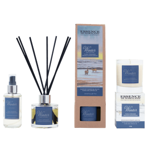 A group of Winter products. A glass bottle of Winter room spray on the right, then a glass diffuser bottle of Winter with black fibre reeds, in the middle the diffuser box packaging detailing the name of the product and an image of two stags in the snow, a similar image is on the box packaging for the candle on the right hand side with the candle sat on top.