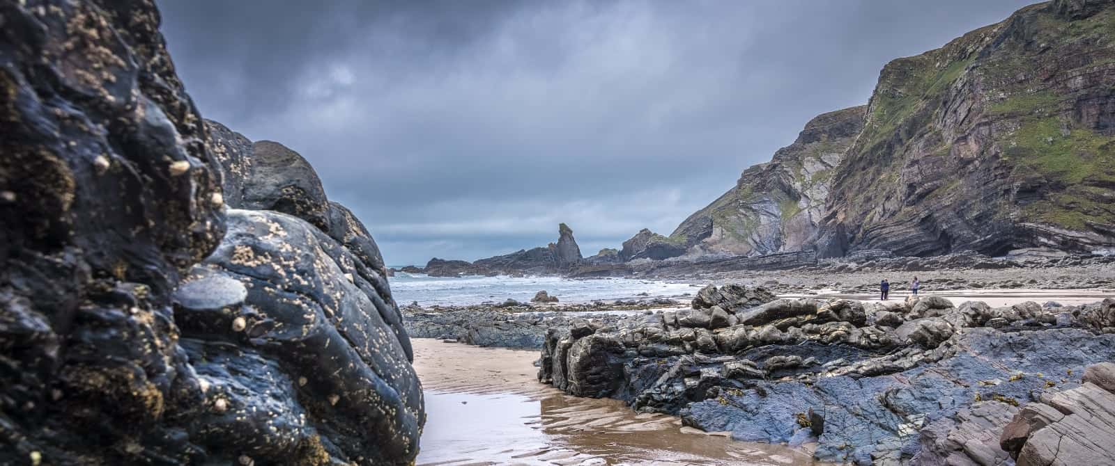 Panoramic view of the beach at Hartland Quay. A view of Bear Rock which is pointed. A group of people are standing on the beach in the background just below the cliffs. The image is mainly blue in tone and atmospheric.