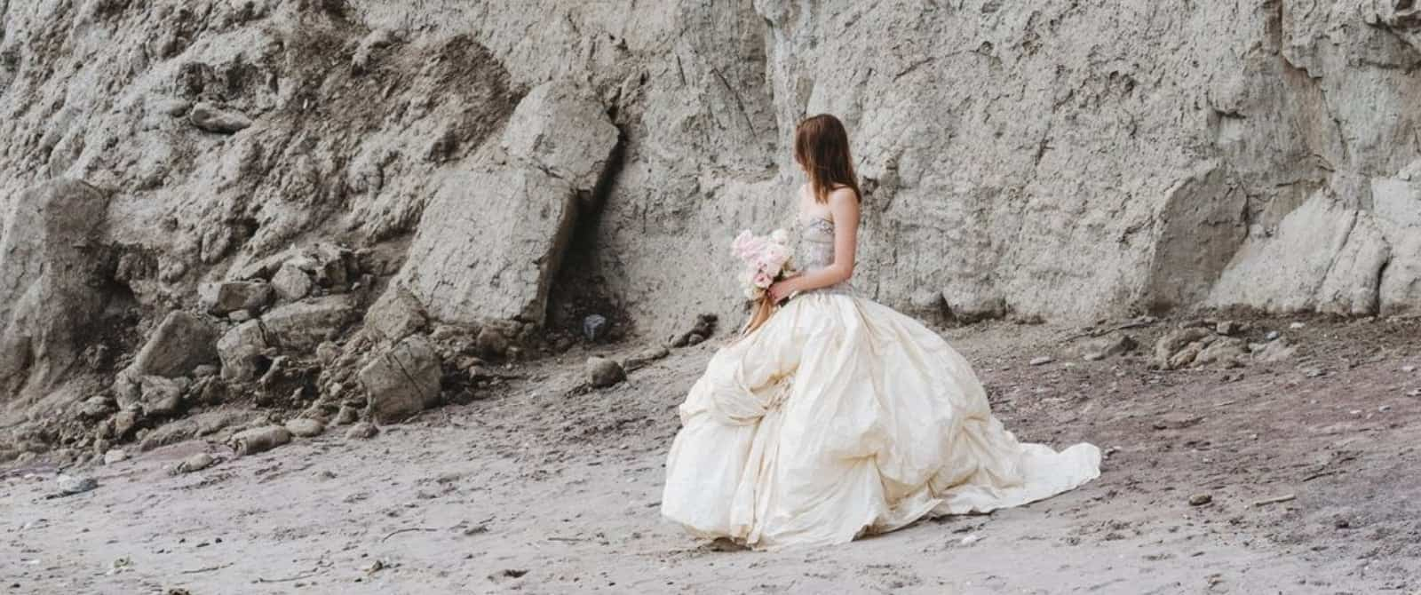 A bride whose face is turned away from the camera. Stood on a rocky beach with cliffs in the background.