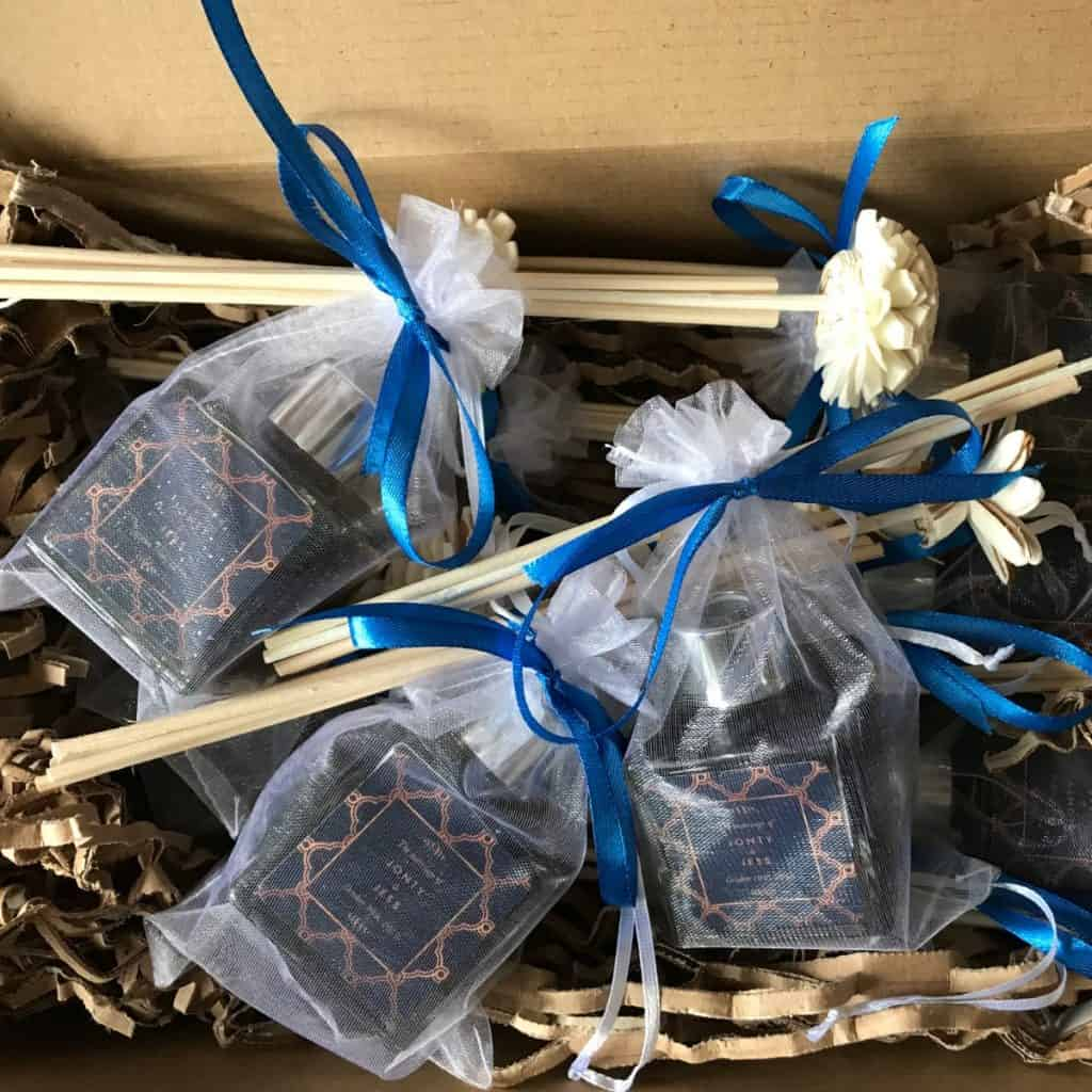 An open cardboard box containing 3 50ml diffuser bottles with customised labels for Jonty and Jessica's wedding. Packaged inside organza bags with blue ribbon tied around the top also securing some rattan reeds with rattan flower heads.